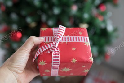 A gift box is holding by hand.