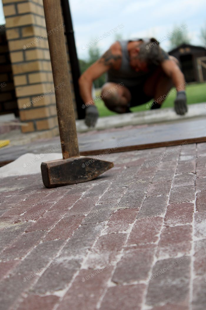 Man paving a brick pathway