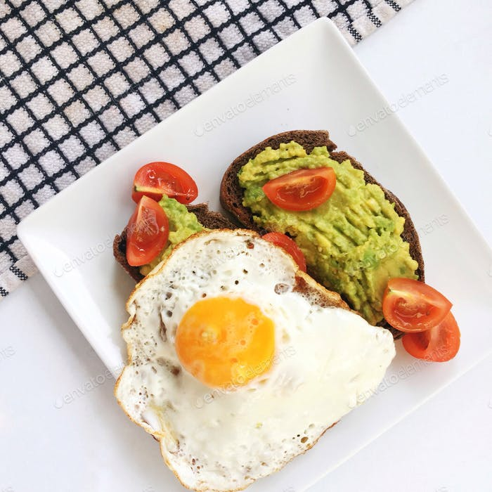 A square plate of breakfast including a fried egg with tomatoes and avocado on toast