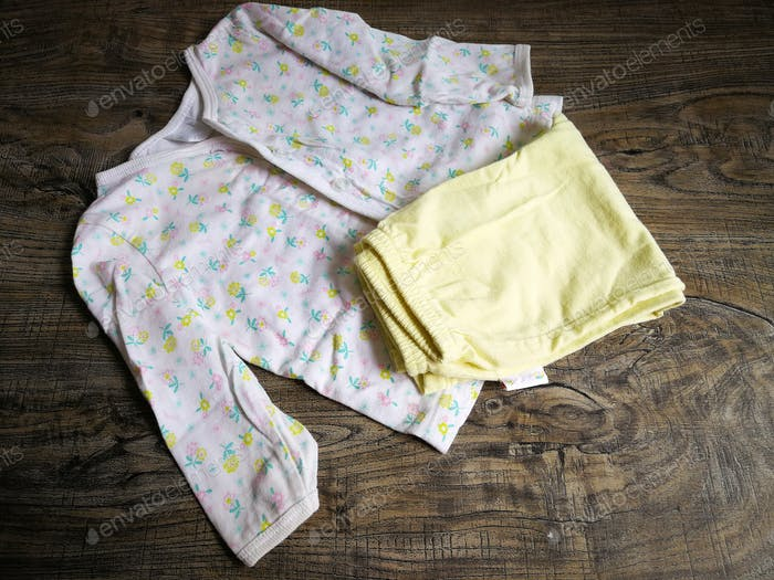 flat lay of baby apparel on wooden background