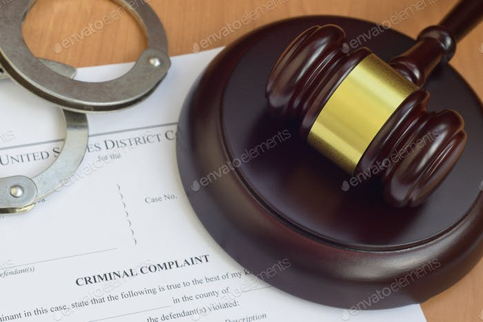 Justice mallet and criminal complaint blank document with police handcuffs close up
