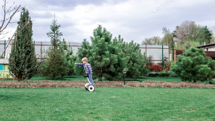 Child riding on self-balancing hover board on the backyard of cottage