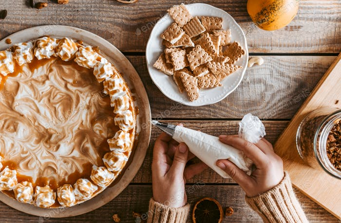 Flat lay of hands holding piping bag and decorating pumpkin cake on rustic wooden background.