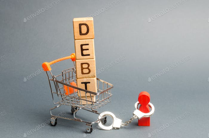 Wooden blocks with the word Debt in a supermarket trolley and a human figurine bound by handcuffs