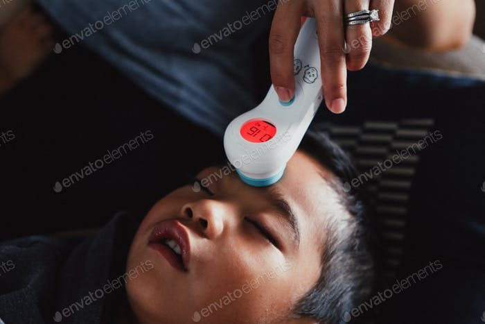 Diverse little boy child sick with fever and cold flu mom taking temperature high fever.