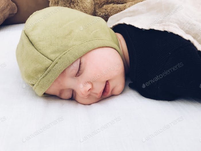 Sleeping baby with a tiny little grin