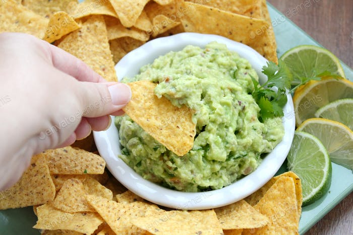 Enjoying a chip and dip - guacamole and a beer for Superbowl