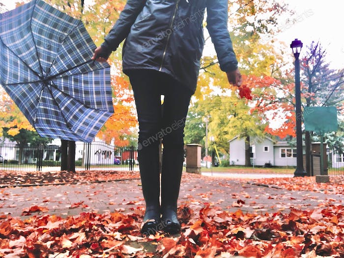 Woman is standing in a pile of autumn fallen leaves, holding a plaid umbrella and a maple leaf in a