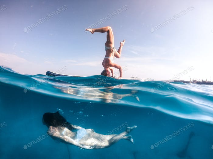 Paddleboard yoga with girl swimming underneath