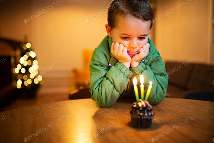sad little boy looking at a birthday cupcake and crying because no one came to his party