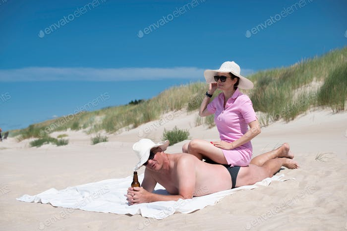 Attractive happy couple relaxing on the beach-man drinking beer and woman sitting on his back