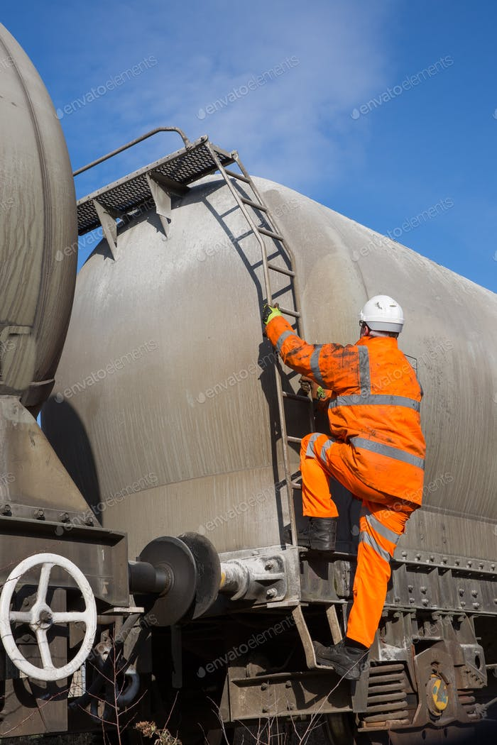railway or manual worker climbing a ladder on the side of a freight tanker wagon to inspect high up