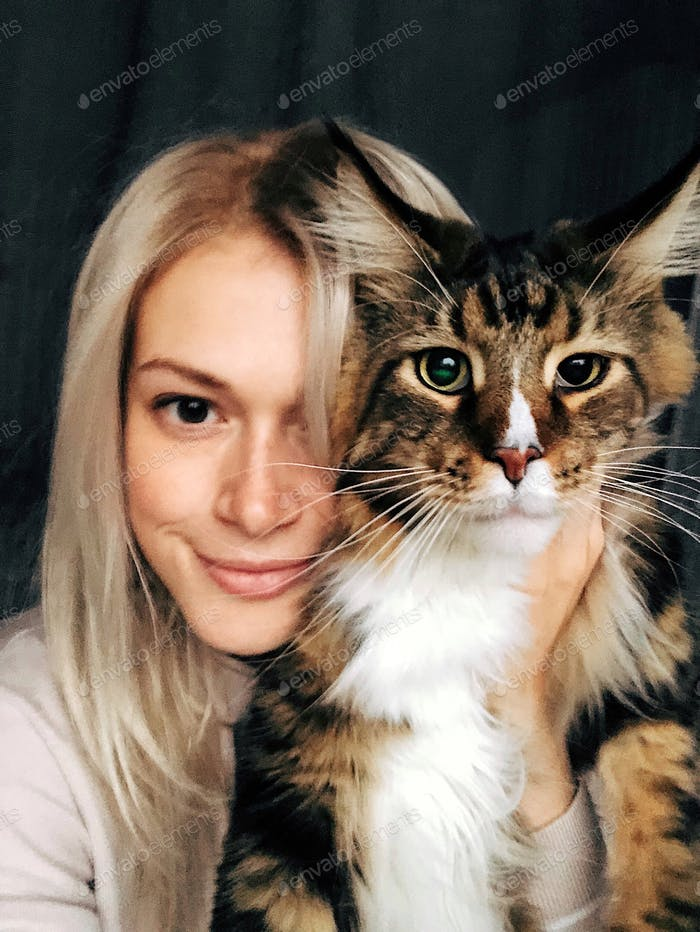 Pretty blonde girl sitting with big tobby cat. Hugging with adorable pet. cute domestic animal. Gian