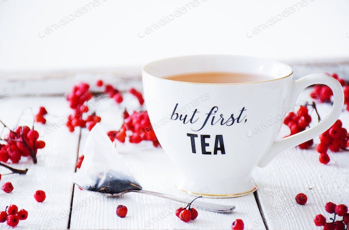 Teacup that say But First Tea surrounded by red berries