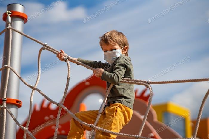 New normal. Preschooler boy on the playground
