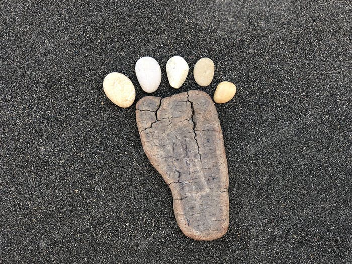First step, conceptual artistic composition with pebbles and wood material in form of a foot