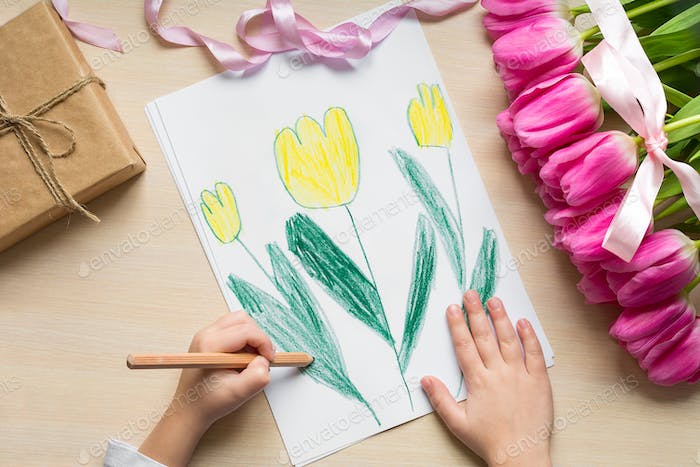 Little boy paints greeting card for Mom on Mother's Day or 8 March. Top view