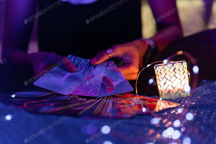 Woman's hands holding three tarot cards for a reading with fanned out cards