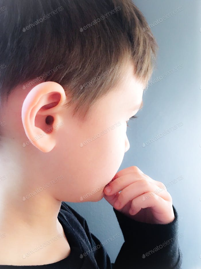 Side view profile headshot of young boy's right ear. Looks to be in contemplation.