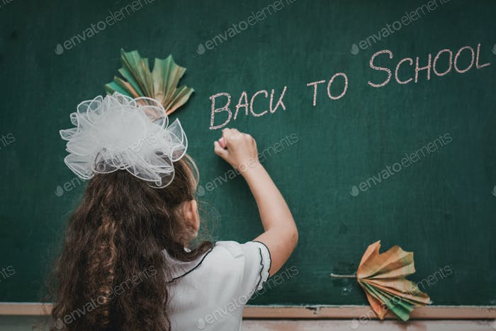 """Female child writes word on the board """"Back to School""""."""