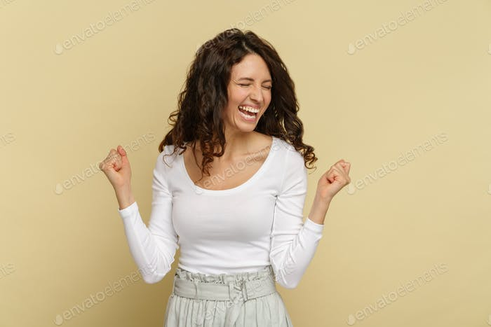 Overjoyed woman emotion of triumph with toothy smile, closed eyes, hold fists up celebrate success