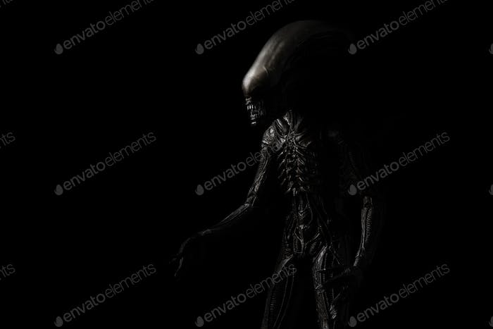 Alien (xenomorph) comes out of the dark shadow (close up)