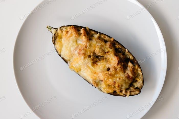 Halbe Aubergine gefüllt mit Fleisch mit geriebenem Käse in einer weißen Schüssel