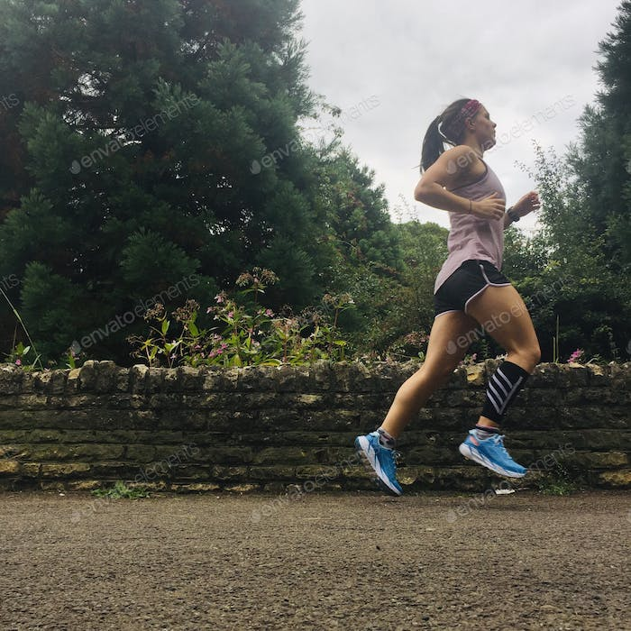 Millennial woman exercising by running outdoors