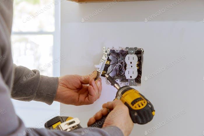 Arbeiten Sie an der Installation von Steckdosen mit elektrischen Leitungen und Steckverbindern in Gipskartonplatten