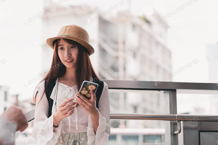 Beautiful Asian traveler using smartphone in front of public transportation station.