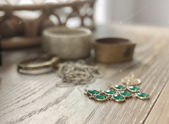 Gold jewelry laid out on dresser