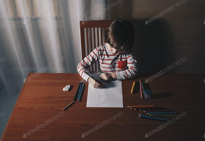 Vorschüler Junge Zeichnung auf dem Tisch in seinem Haus, von oben gesehen.allein, zu Hause, kaukasisch, Kind,