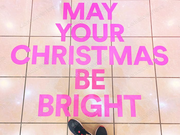 Photo 2 of 3 - Bright pink wild words in capital letters on the floor of a retail store: MAY YOUR