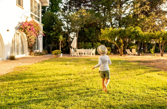 Little barefoot boy running on grass in holiday house. Summer holidays healthy lifestyle