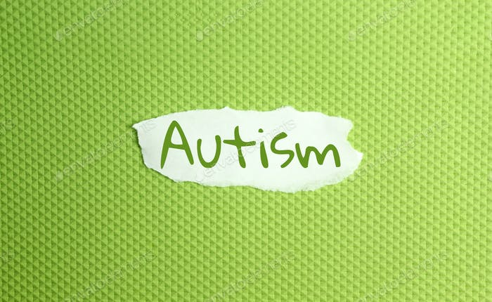 a torn paper written with inscription autism on a green background