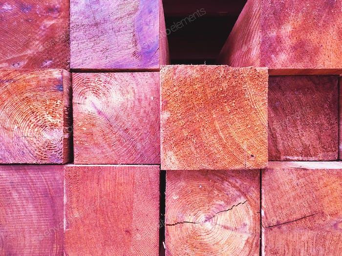Enden von Schichten von quadratischen Schnitten aus rosa Holz mit Holzmaserung Textur zeigt.