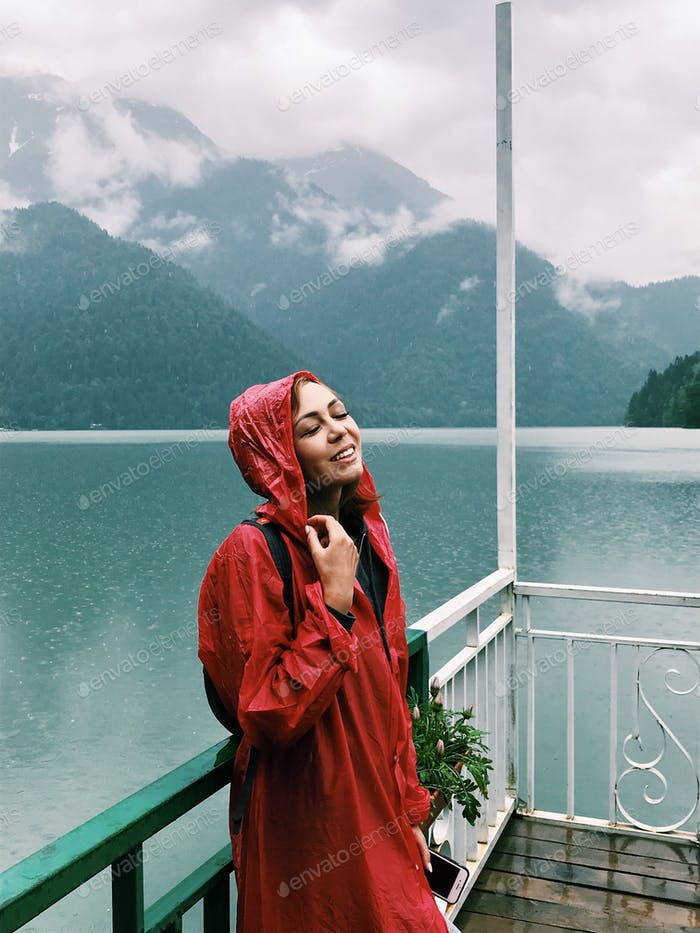 Coaxing woman in a red cloak stands near the lake. Travel, nature