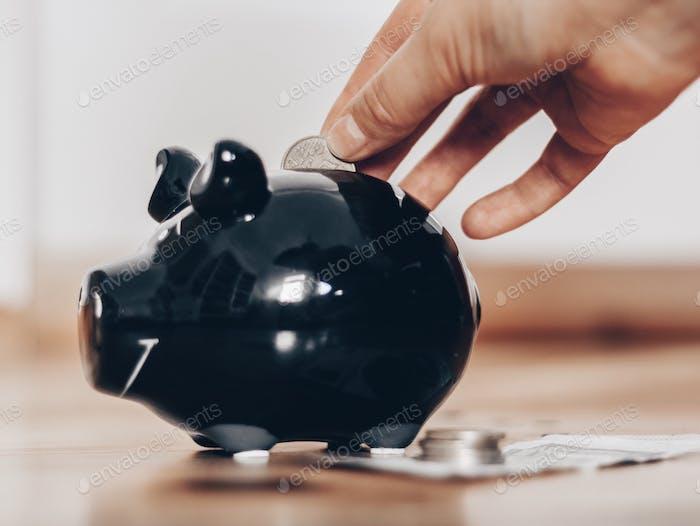 Eine Hand, die eine Münze in ein schwarzes Sparschwein steckt