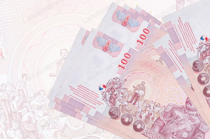 100 Thai Baht bills lies in stack on background of big semi-transparent banknote. Abstract presenta