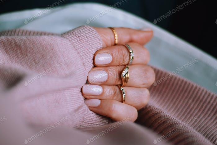 Blush pink nails with sparkles, gold rings and a pink sweater