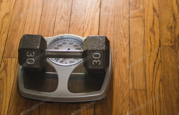 Exercise fitness concept, dumbbell on analog scale