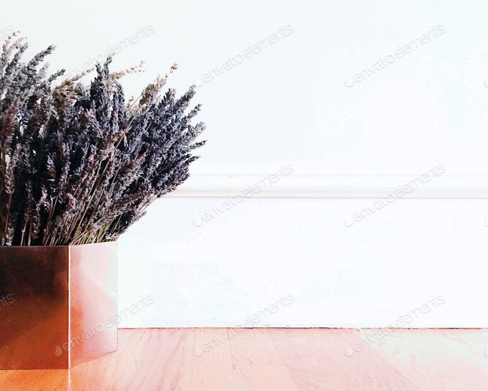 Dried lavender blossoms gathered in a shiny metallic copper pot on red oak floors against a bright