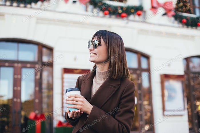 Woman drinking coffee in festive holiday decorated city