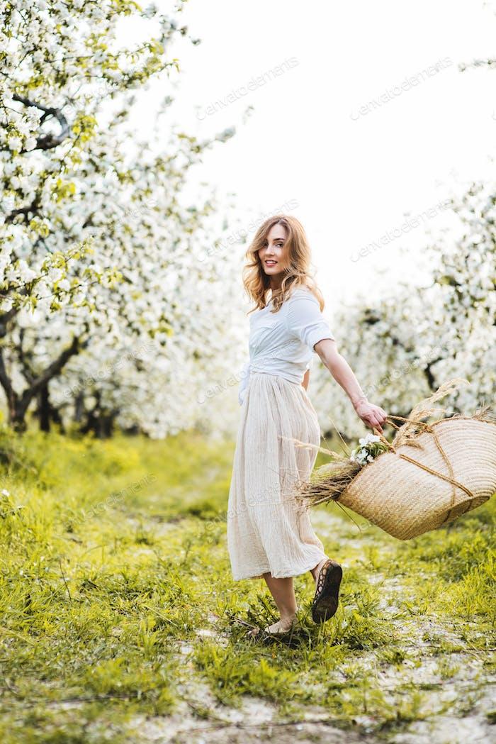 Beautiful smiling woman in blooming spring garden