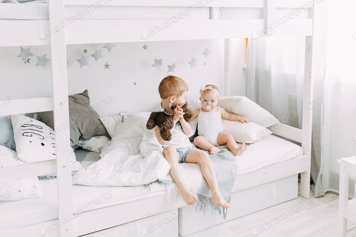 brother and little sister in the children's playroom bedroom, boy and girl infant