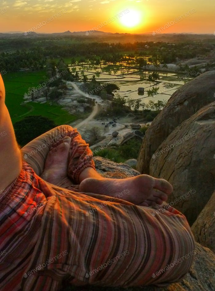 Yogi in lotus position on the rocky boulders outside Hampi, Karnataka, India