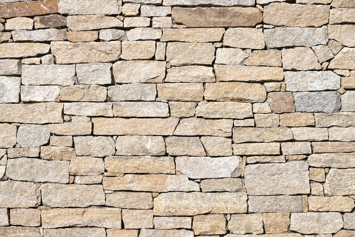 Neutral natural stacked stone stonewall texture background, abstract pattern contrast