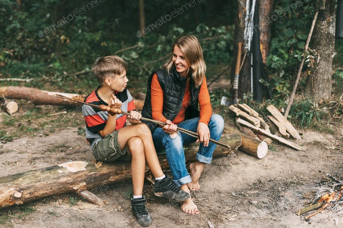 A mother and her teenage son are sitting on a tree in campsites and trying grilled sausages cooked