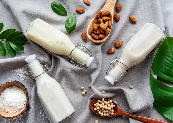 Bottles with different plant milk - soy, almond and coconut milk.
