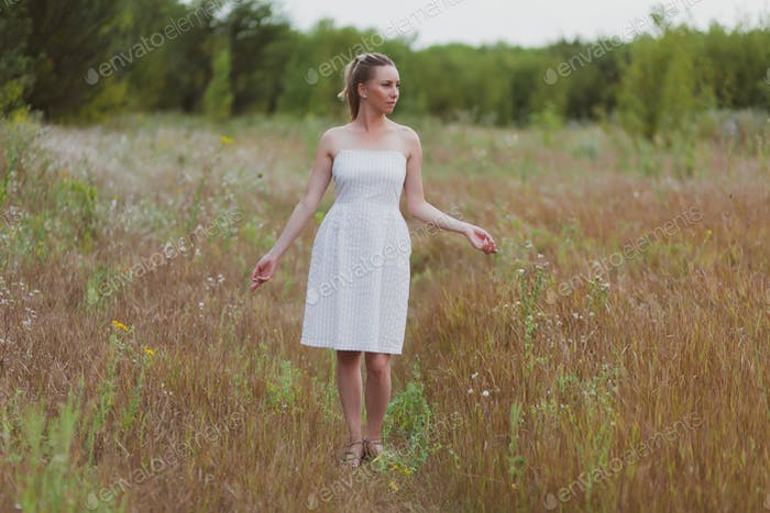 adorable young woman in a white dress is walking in a wheat field